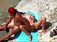 Couple of mutually masturbating to orgasm at a public beach